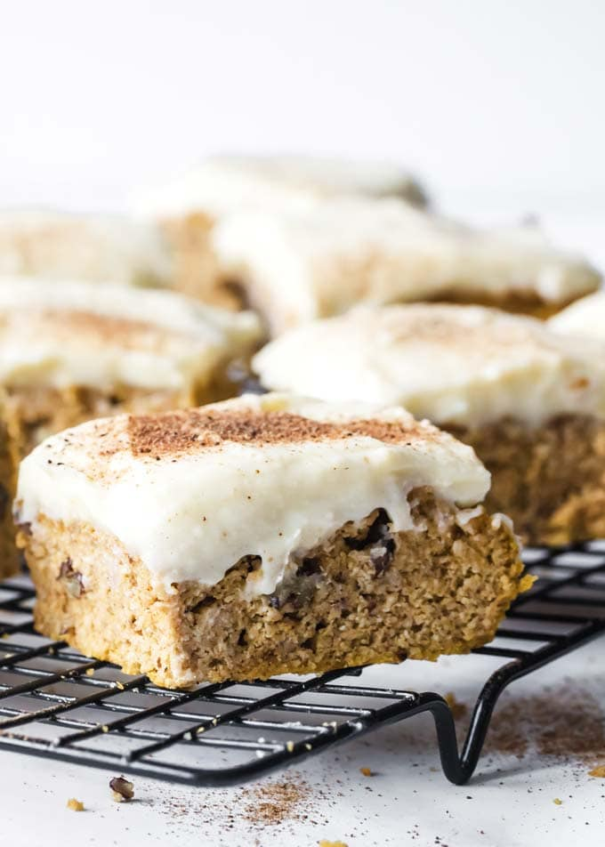healthy pumpkin bars with cream cheese frosting on a cooling rack