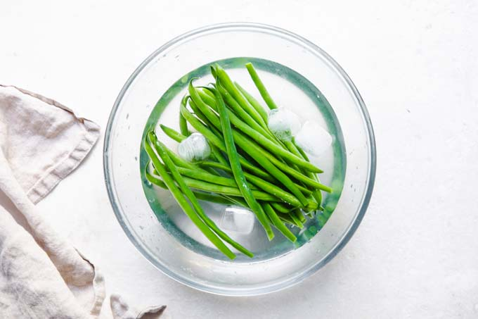 cooling green beans in a glass bowl filled with water and ice cubes