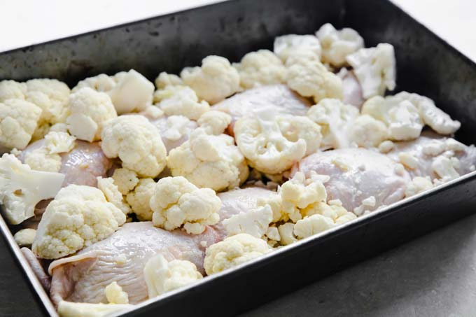 chicken thighs and cauliflower in a baking tray