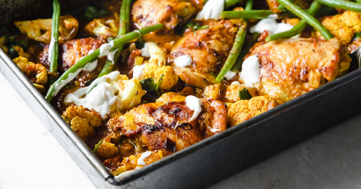 curry chicken and vegetables in a baking tray topped with yoghurt