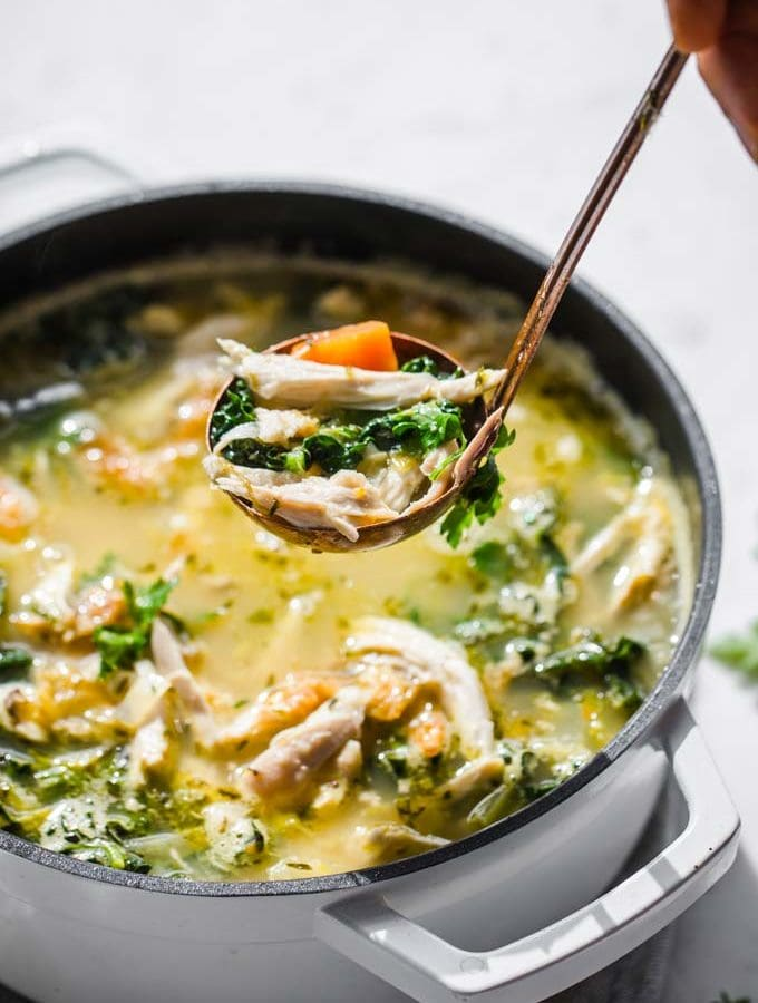 a pot of keto chicken soup and a ladle lifting soup