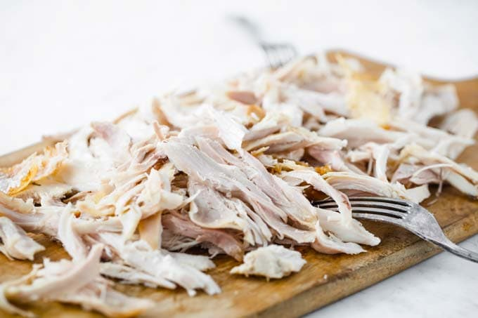 shredded roast chicken on a wooden board