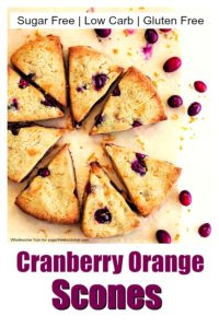 Cranberry orange scones on parchment paper with scattered cranberries and orange zest