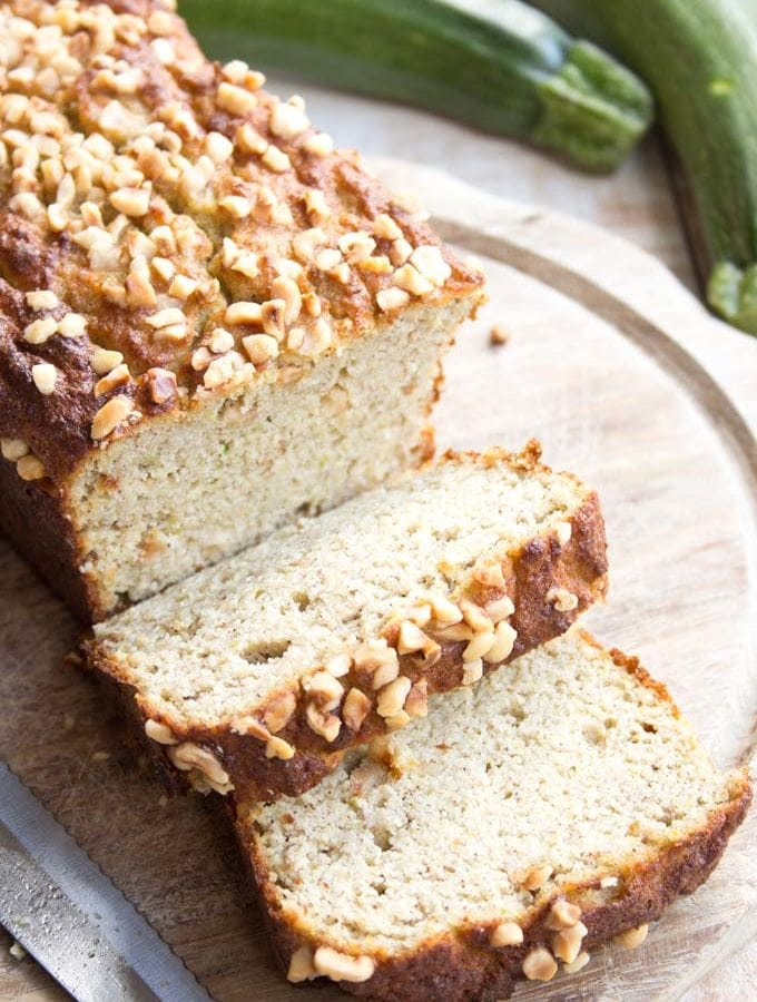 A keto zucchini bread topped with hazelnuts with two slices cut off on a wooden board and a knife