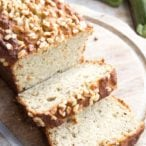 a keto zucchini bread studded with hazelnuts cut open on a wooden board