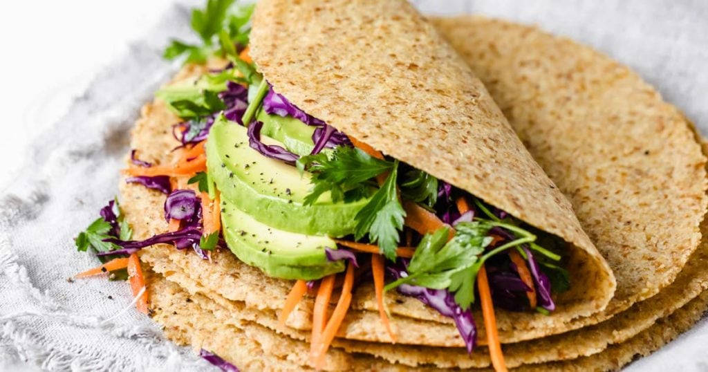 a stack of keto tortillas, the top tortilla is filled with sliced avocado, carrots, lettuce and other