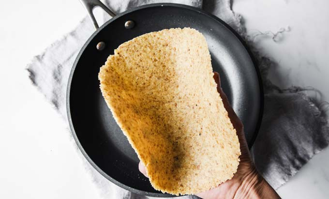 hand holding pliable low carb tortilla over a frying pan