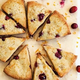 sugar free cranberry orange scones on parchment paper and scattered fresh cranberries