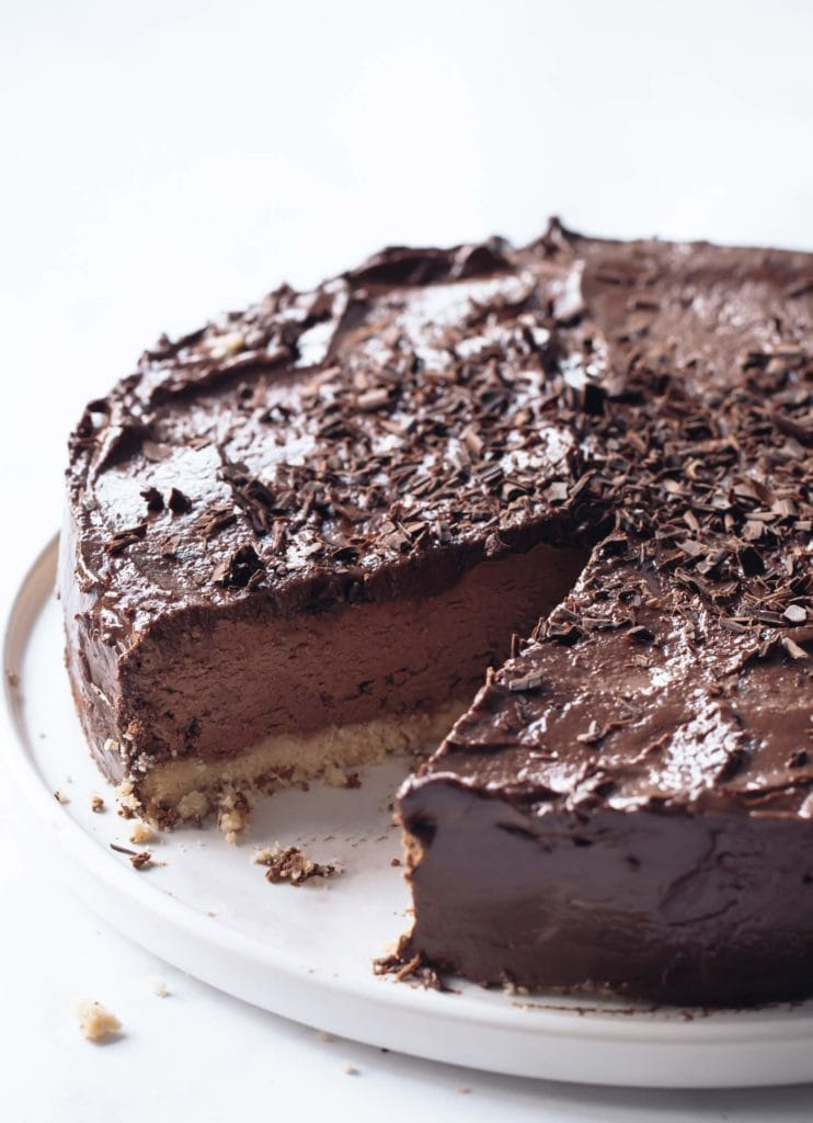 a keto chocolate cheesecake with chocolate flakes on a white serving platter