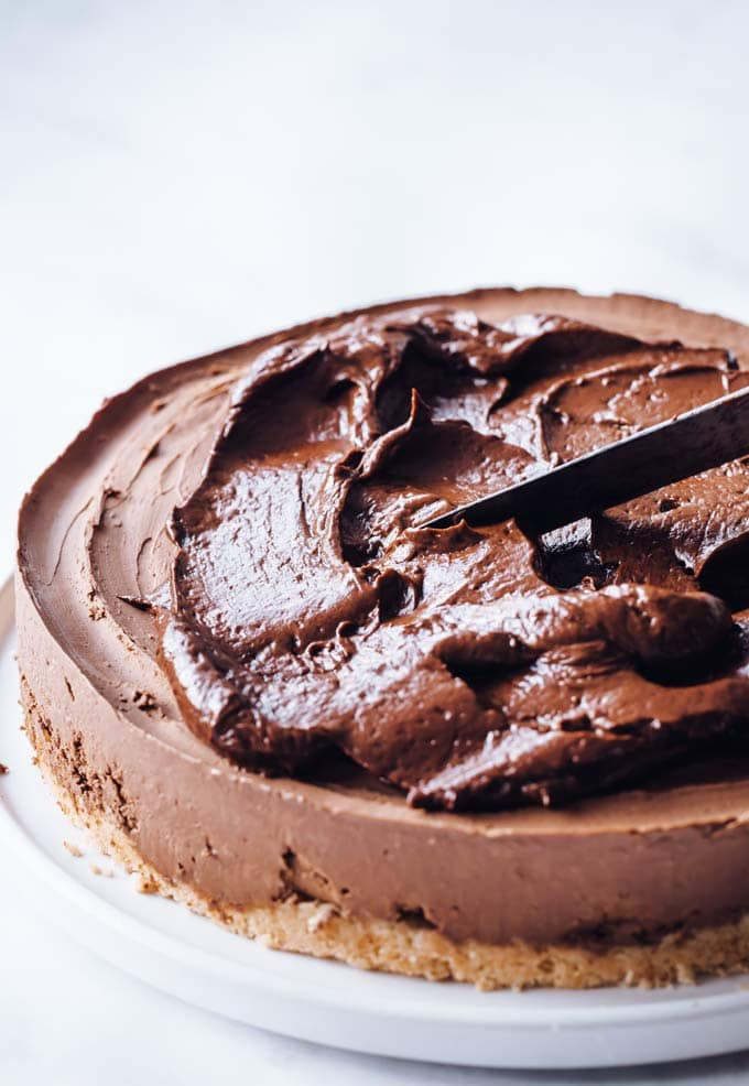 chocolate ganache being spread onto a chocolate cheesecake with a knife