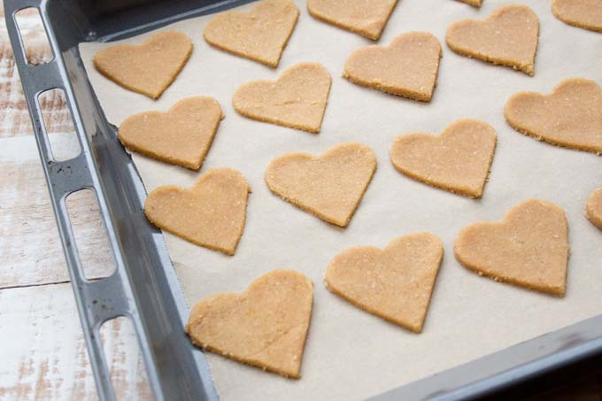 unbaked heart shaped ginger cookies on a baking sheet