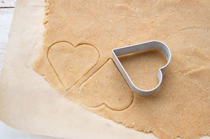 stamped out heart shaped cookie dough and a cookie cutter