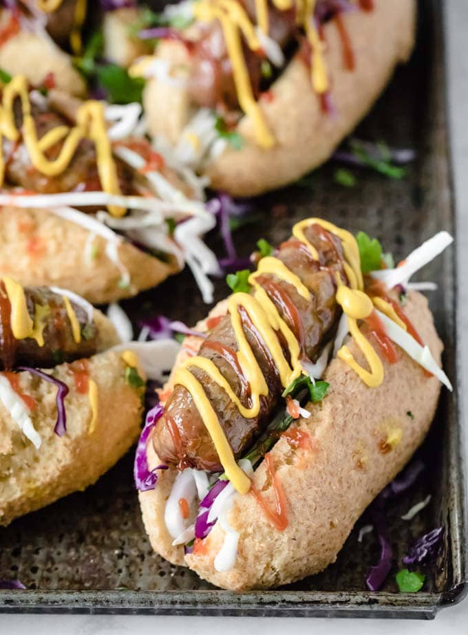 low carb hot dog buns filled with sausage, salad and mustard and ketchup