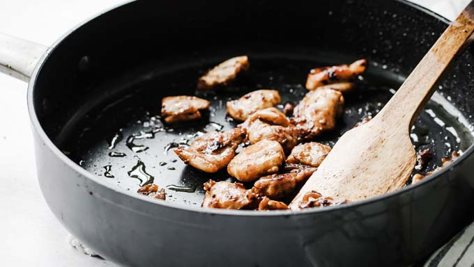 marinated chicken pieces in a frying pan and a spatula