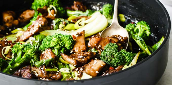 chicken stir fry with broccoli and bok choi in a pan and a spoon