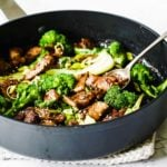 a cast iron pan with keto teriyaki chicken, green vegetables and a spoon