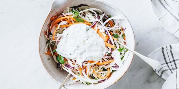 shredded cabbage and carrots with a blob of yoghurt dressing in the centre