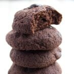 chocolate cookies stacked on top of one another, the top cookie is bitten into