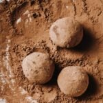three keto chocolate truffles rolled in a bed of cacao powder