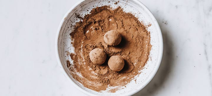 truffles rolled in a bowl with cacao powder
