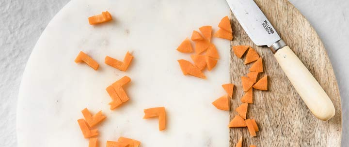 carrot beaks and feet on a cutting board and a knife