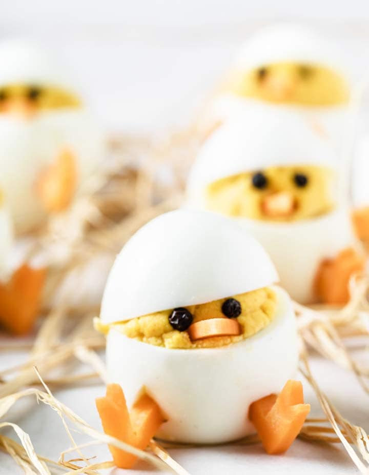 a deviled egg easter chick with peppercorn eyes and carrot feet and beak
