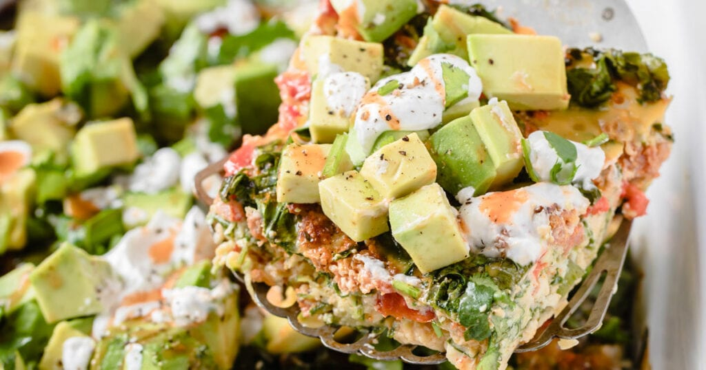 a slice of mexican breakfast casserole topped with avocado, sour cream and hot sauce