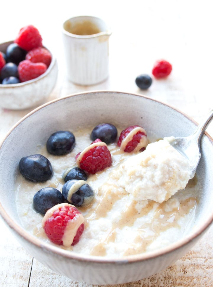 coconut flour noatmeal in a bowl topped with blueberries and raspberries
