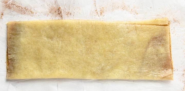rolled out dough rectangle with cinnamon and sweetener in the middle