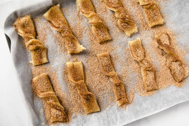 keto snickerdoodle twists dusted with cinnamon on a baking tray