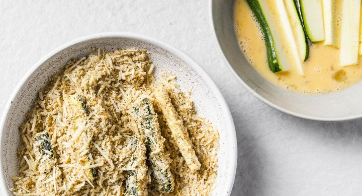 zucchini sticks being coated in a cheese and almond flour mix and another bowl with zucchini sticks in an egg wash