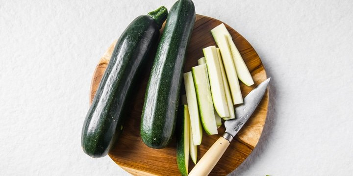 sliced zucchini on a wooden board and a knife