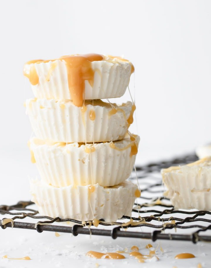 Cheesecake fat bombs stacked on a wire rack topped with gooey caramel sauce