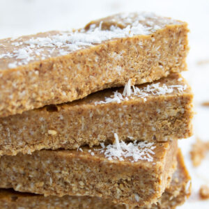 a stack of coconut almond butter bars topped with desiccated coconut