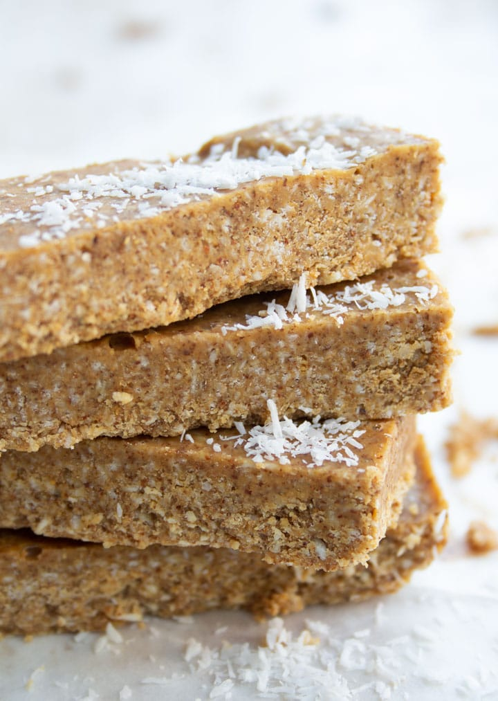 a stack of almond butter bars topped with desiccated coconut