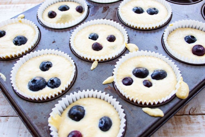 muffin batter in paper cases in a muffin pan with blueberries on top