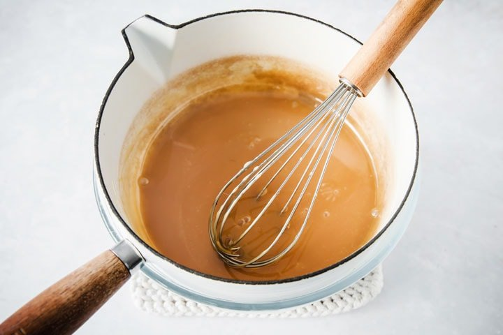 a saucepan with caramel and a baloon whisk