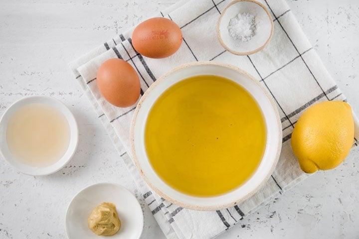 olive oil, eggs, vinegar, mustard and salt in bols and a lemon