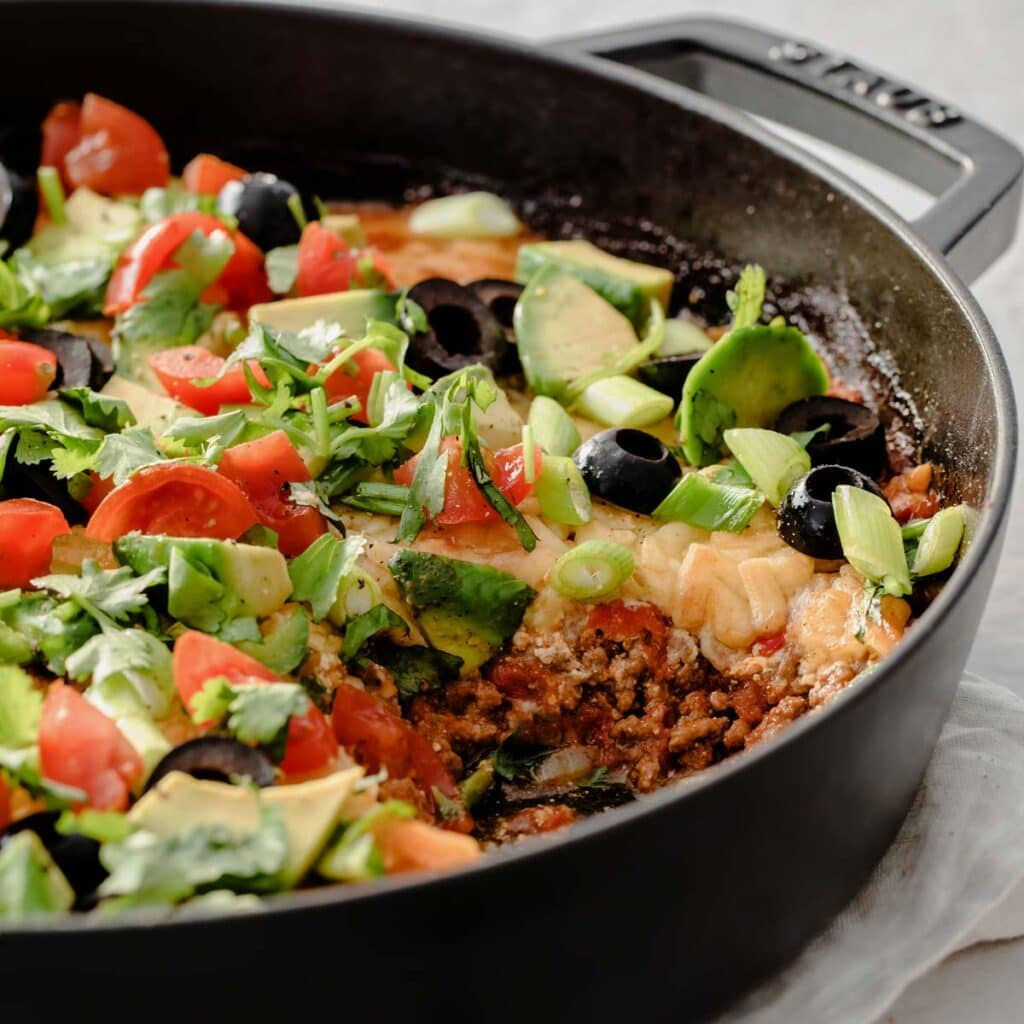 a cast iron pan filled with a ground beef taco casserole topped with melted cheese and toppings