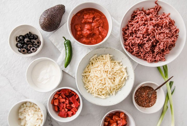bowls with ingredients such as ground beef, peppers and cheese