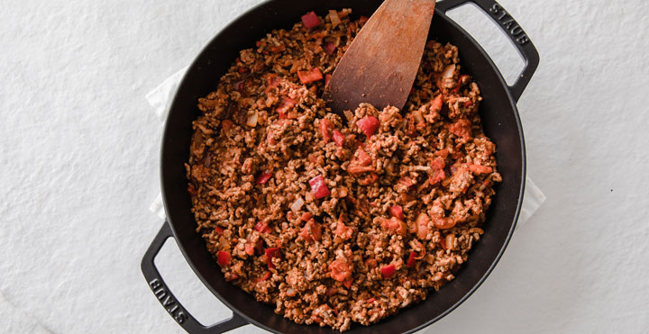 ground beef and peppers in a cast iron pan