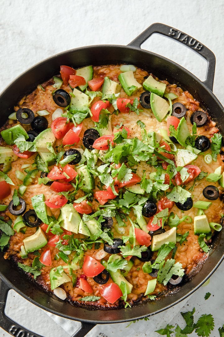 ground beef low carb taco casserole topped with tomatoes, avocado, olives and herbs
