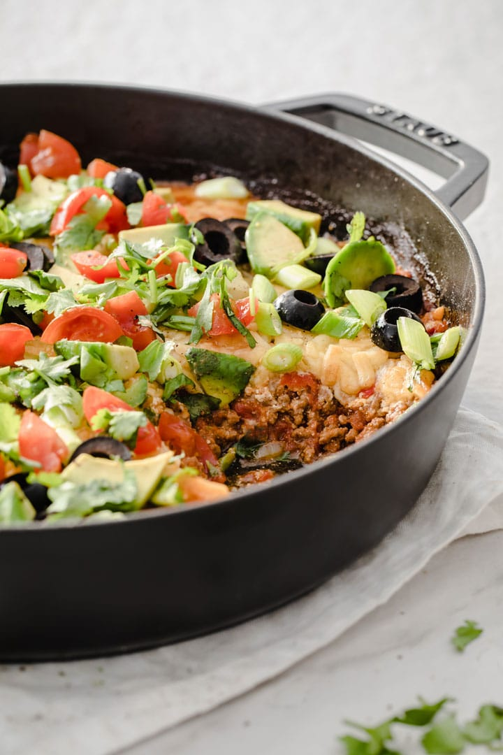a keto taco casserole topped with avocado, tomatoes and herbs in a cast iron pan