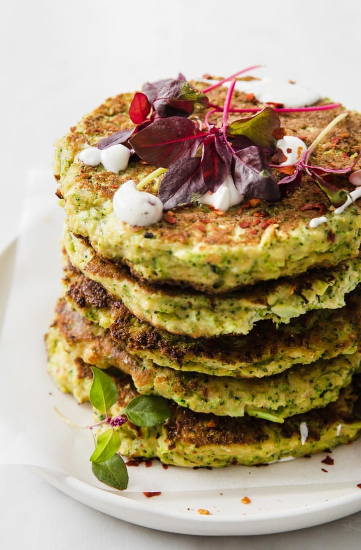 a stack of broccoli fritters topped with micro greens and coconut yoghurt