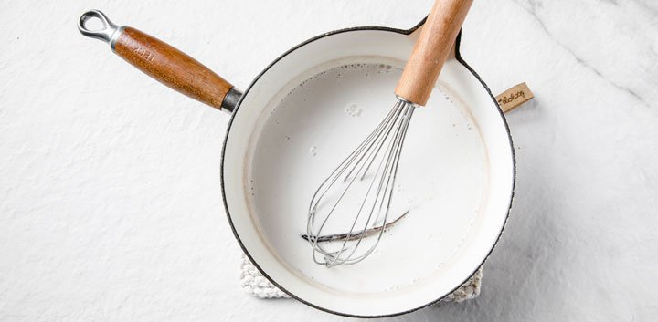 coconut cream and vanilla pod in a saucepan with a whisk
