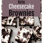 cheesecake brownies cut into squares on parchment paper