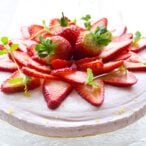 A sugar free strawberry cheesecake topped with sliced strawberries and decorated with mint leaves and lemon zest
