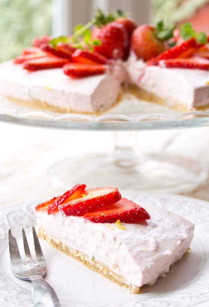 a slice of sugar free cheesecake on a plate with a strawberry cheesecake in the background