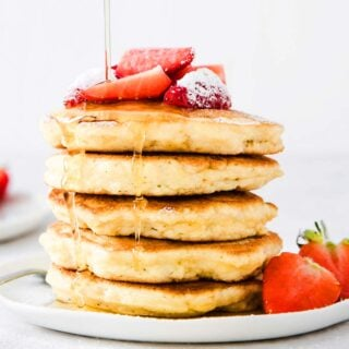 a stack of keto coconut flour pancakes drizzled with sugar free syrup and topped with strawberries