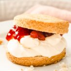 closeup of an almond flour scone cut in half and filled with clotted cream and strawberry jam
